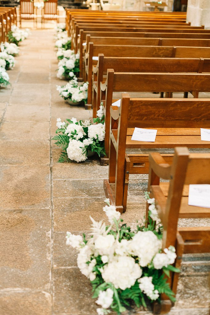 white ground floral arrangements for the aisle