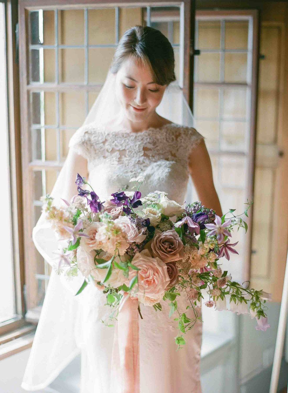 bride with a blush and lavender bouquet